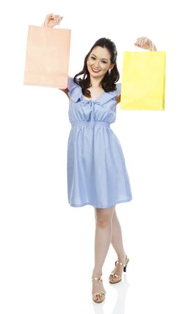 An attractive young woman holding up colorful shopping bags  isolated on white   photo
