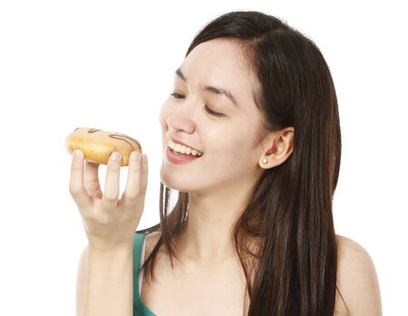 A young pretty woman about to eat a donut  on white background Stock Photo - 15595333