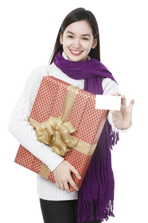 A young woman holding a gift and a blank card  on white background   photo