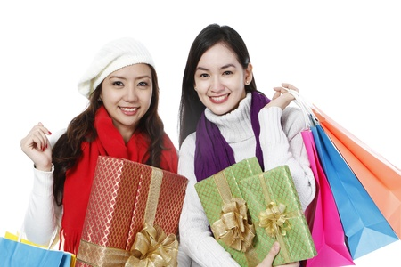 Two young women in winter clothing carrying gifts and shopping bags  on white background   photo