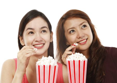 Two young women eating popcorn while watching a movie  on white background   photo
