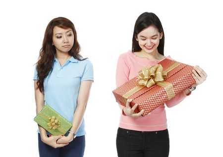 celos: Una mujer joven que sostiene un pequeño regalo, envidioso de la presente mucho más grande de un amigo en el fondo blanco