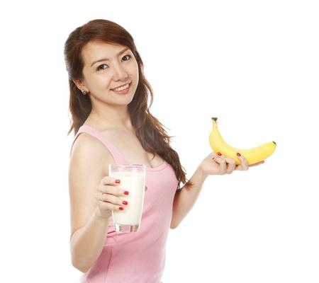 Een geschikte jonge vrouw met een banaan en een glas melk op een witte achtergrond Stockfoto - 15595318