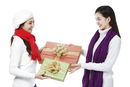 白い背景の上に贈り物を交換する 2 つの若い女性