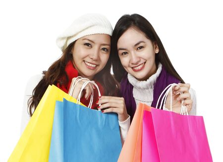 Two young women in winter clothing holding colorful shopping bags  on white background   photo
