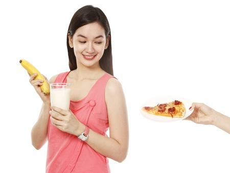 白い背景の上の健康と不健康な食べ物との間を選択します。