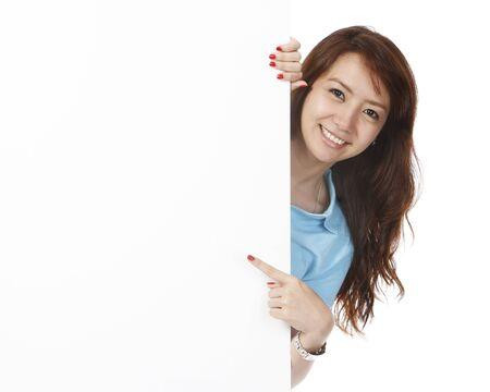 Een jonge vrouw wijzend op een lege witte muur Stockfoto - 15595319