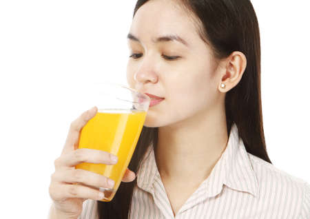 A young woman drinking a glass of fresh orange juice Stock Photo - 15762701