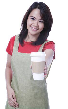 delantal: Una joven camarera que sirve caf� en una taza desechable Foto de archivo
