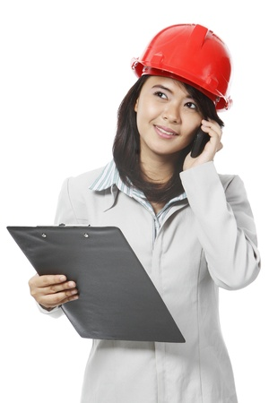A young woman wearing a hardhat and using a mobile phone.