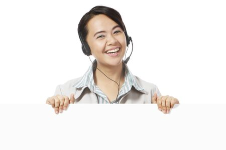 Cheerful young woman wearing a headset and above a blank space.  photo