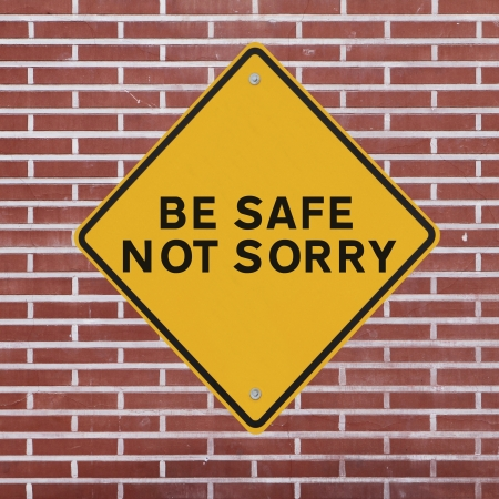 Workplace safety reminder on a red brick wall background  Stockfoto