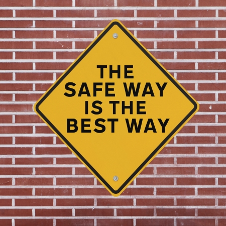 safety slogan: A workplace safety reminder on a red brick wall  Stock Photo