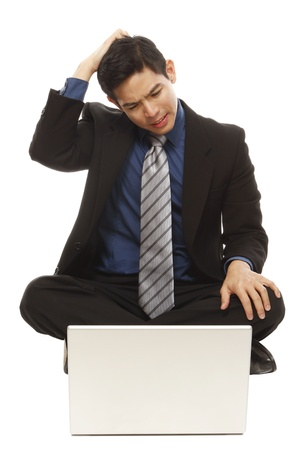 computer problem: A puzzled businessman looking at his laptop