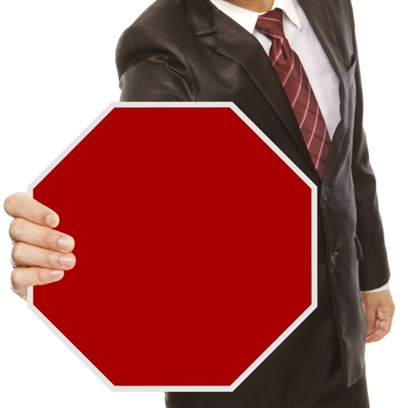 do not enter warning sign: A man in business attire holding a blank Stop sign