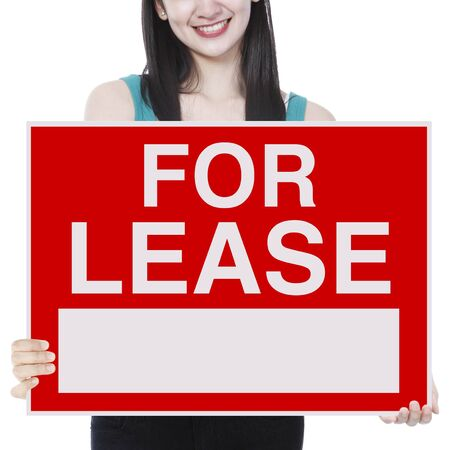 A young woman holding a signboard indicating For Lease  photo