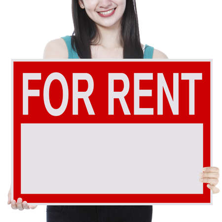 A young woman holding a signboard indicating For Rent  photo