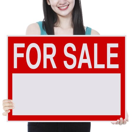 A young woman holding a signboard indicating For Sale  photo