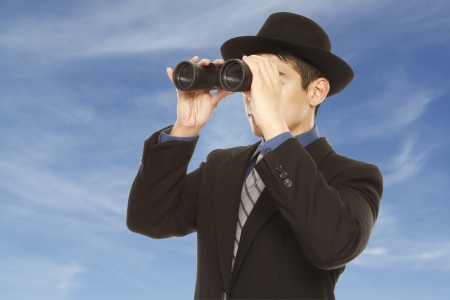 A man in business attire and hat using binoculars  against a dramatic sky background   photo