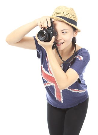 taking photograph: A smiling teenager using a camera. Readable logos removed.  Stock Photo