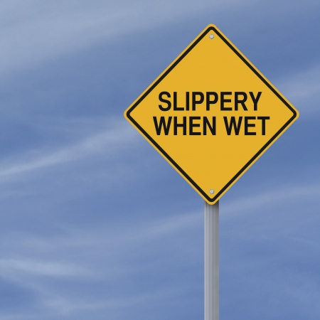 Slippery When Wet road sign against a blue sky background Stock Photo - 19732218