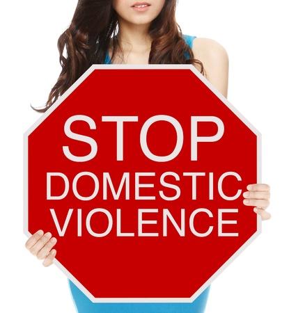 violencia intrafamiliar: Una mujer que sostiene una se�al de stop conceptual de abuso dom�stico o violencia
