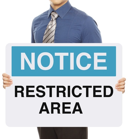 A man holding a notice sign indicating Restricted Area  photo