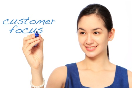 A woman writing about customer focus  photo