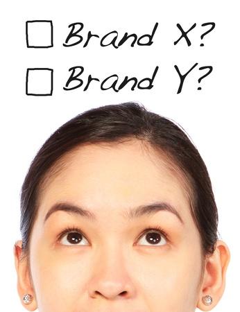 どのブランドを選択するか購入するの考える若い女 写真素材