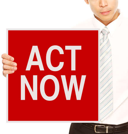 A businessman holding a sign indicating Act Now  Stock Photo