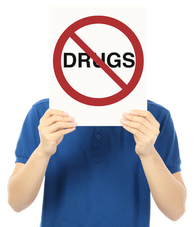 illegal drugs: An unrecognizable young man holding up a signboard against illegal drugs  Stock Photo
