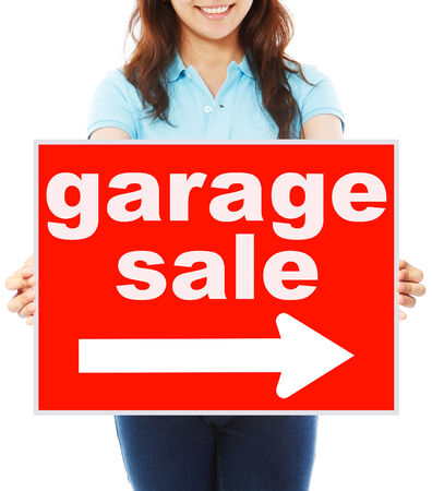 A young woman holding a signboard indicating Garage Sale