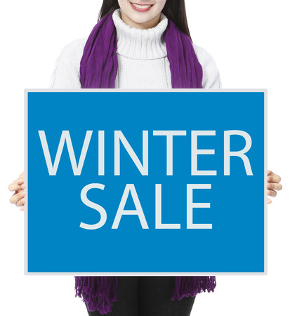 A woman holding a sign indicating Winter Sale photo