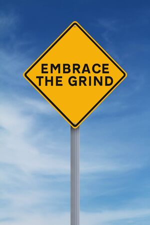 grind: A modified road sign indicating Embrace The Grind Stock Photo