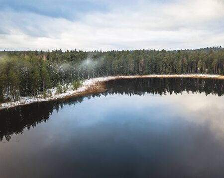Aerial Drone Photograph of a Partly Frozen Lake in a Snowy Winter Day