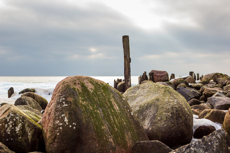 Jetty Pillars and Rocks Covered witn Snow in a Cloudy Winter Day with a Few Sun Beams Shining on Them and a Sea in a Background