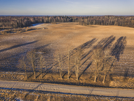 Aerial Drone Photography of a Countryside Road in Sunny Winter Day with a Little Snow on the Sides an Trees in the Background - vintage look edit