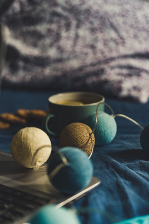 Tea with Lemon and Cookies with Chocolate Laying on Mattress - Christmas Decoration Light Balls and Grey Laptop Besides it, Vintage Look Edit 写真素材