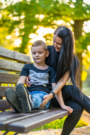 Kid Sitting on a Park Bench with His Mom  in Autum with Colorful Background in a Sunny Day - Caption on Shirt