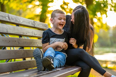 Mom Tickles Her Son on a Park Benck  in Autum with Colorful Backgroun in a Sunny Day, Both Laughing- Caption on Shirt