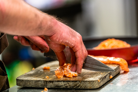 Male Chef Cutting Fresh Salmon on the Wooden Board with Blurred Pan in a Background - Isolated Action with Only Hands Showing, Kitchen Set
