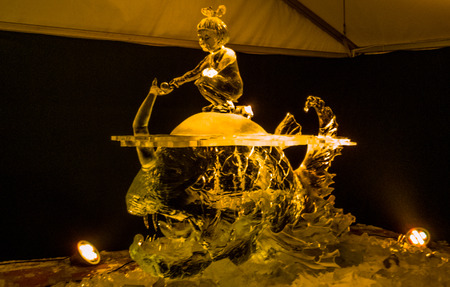 Jelgava / Latvia - February 10th, 2017: Big Carved ice sculpture - girl surfing a piranha, at night of International Ice Sculpture Festival in Jelgava - yellow light