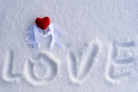 Isolated Origami Paper Boy and Girl Holding Hands With a Red Heart Between Them on the White Snow Background with Space for Text - Concept of Love, Happiness and Joy on Valentines Day Stock Photo
