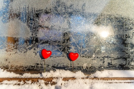 Blurred Read Heart Decorations on the Foreground of Window with Hoarfrost - Abstract Background with the Space for Text, Concept of Love and Happiness on Valentines Day Stock Photo
