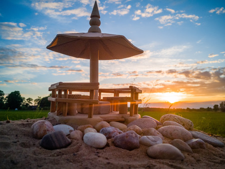 Handmade Wooden Shed Model on the Beach Sands with Stones In Front of it with Dramatic Sunset in Skies Behind it - Concept of Harmony and Peace with a Space for Text