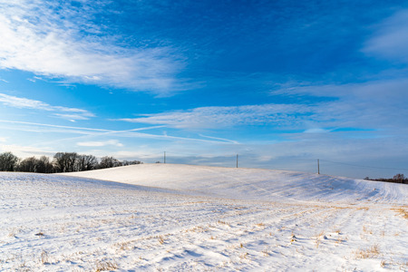 Empty Countryside Landscape in Sunny Winter Day with Snow Covering the Ground with Power Lines in Frame, Abstract Background with Deep Look - Concept of Fun and Joy