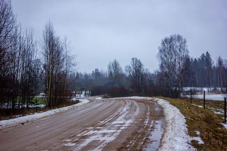 Empty Countryside Landscape in Cloudy Winter Day with Snow Partly Covering the Ground and Fog, Puddles and Tire Marks on the Road - Concept of Sadness and Loneliness