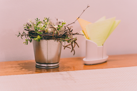 Isolated Handmade Easter Decorations (Bunny with Blossom Flowers in a Bucket on Table with Napkins Beside), Space for Text or Company Logo - Concept of the Harmony and Peace in Family on Festive Time