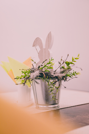 Isolated Handmade Easter Decorations (Wooden Bunny with Blossom Flowers in a Bucket on Table), Space for Text or Company Logo - Concept of the Harmony and Peace in Family on Festive Time
