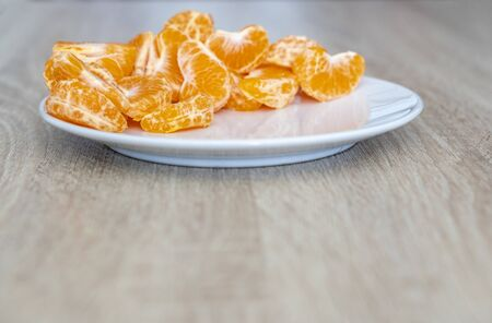 Pealed mandarin peaces on white plate, wooden desk surface, copy space for text